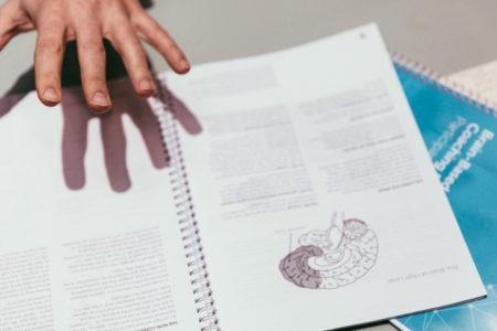 valmennuskirja ja käden varjo